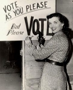 A vintage photo of a woman at a voting sign